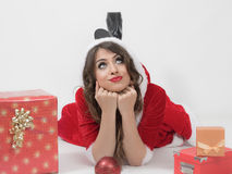 Pensive Santa woman lying prone looking up with head resting on hands and gifts around Royalty Free Stock Images