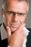 Pensive satisfied mature man. Confident pensive mature man with glasses looking at camera satisfied Stock Photos