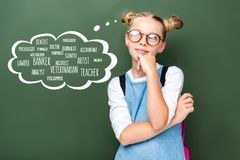 pensive schoolchild in glasses looking up near blackboard with different professions royalty free stock image