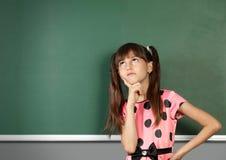 Pensive schoolgirl near blank school blackboard Royalty Free Stock Images