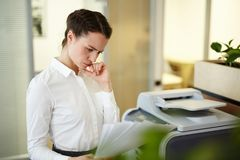 Secretary with papers. Pensive secretary or accountant reading financial documents in office Royalty Free Stock Photography