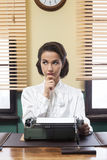 Pensive secretary with typewriter Royalty Free Stock Images