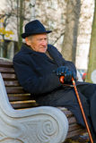 Pensive Senior. Pensive old man in a hat sitting on a bench Stock Image