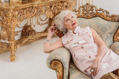 Pensive senior lady relaxing on confortable armchair Stock Photo