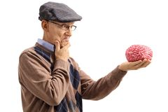 Pensive senior looking at a brain model royalty free stock images