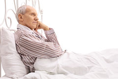 Pensive senior lying in bed royalty free stock photography