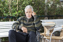 Pensive Senior Male Patient Sitting In Wheelchair At Lawn Royalty Free Stock Photo