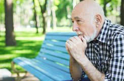 Pensive senior man outdoors. Thoughtful senior man outdoors. Elderly man in casual sitting on the bench in sunny park, copy space, closeup stock photos