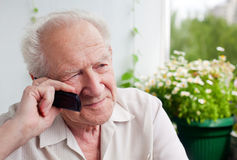 Pensive Senior Man With a Phone. Pensive senior man speaking on the phone with somebody Stock Photo