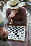 Pensive senior man playing chequers with his friend. Top view of serious male pensioner thinking about next move in checkers. He is sitting at table and touching Stock Images