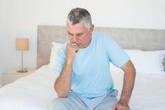 Pensive senior man sitting on bed Stock Photos