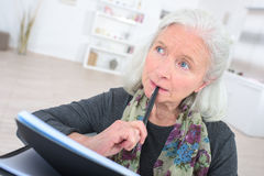 Pensive senior  with notepad Royalty Free Stock Photo