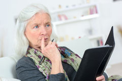 Pensive senior  with notepad Royalty Free Stock Images