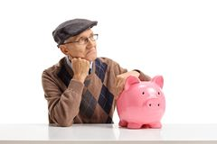 Pensive senior with a piggybank seated at a table. Isolated on white background Royalty Free Stock Photos