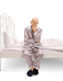 Pensive senior sitting on a bed Stock Image