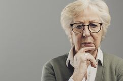 Pensive senior woman thinking with hand on chin. She is sad and concerned royalty free stock images