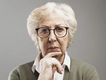 Pensive senior woman thinking with hand on chin. She is sad and concerned stock photos