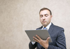 Pensive and serious businessman looking message in tablet comput Stock Image