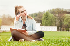 Pensive serious woman sitting outside and writing in her diary Stock Images