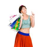 Pensive shopping woman holding bags and smiling Stock Images