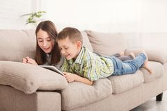 Pensive siblings reading book lying on sofa royalty free stock photo