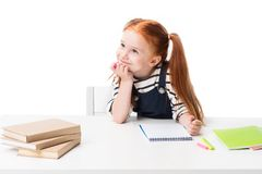 Pensive smiling schoolgirl drawing with felt tip pens and looking away. Isolated on white royalty free stock photo