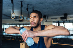 Pensive sports man holding bottle with water in the gym Stock Image