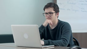 Pensive student with laptop studying in the university library stock footage