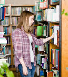 Pensive student in the library surrounded by books Stock Photo