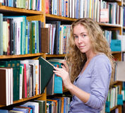 Pensive student in the library surrounded by books Stock Images