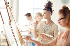 Something is wrong. Pensive student with palette and paintbrush looking attentively at painting on easel Stock Photography