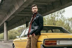 Pensive stylish man in leather jacket standing near vintage car. And looking away stock photos