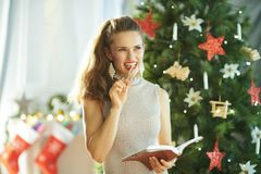 Pensive stylish woman with notebook and pen near Christmas tree royalty free stock images