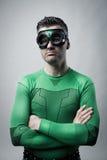 Pensive superhero with arms folded. Sad pensive superhero in green costume with arms folded stock image