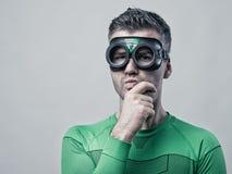 Pensive superhero with hand on chin Stock Image