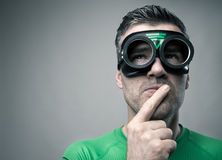 Pensive superhero with hand on chin Royalty Free Stock Photography