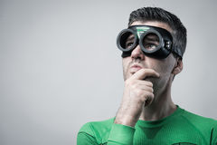 Pensive superhero with hand on chin Royalty Free Stock Images