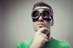 Pensive superhero with hand on chin Royalty Free Stock Photos