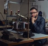 Pensive tailor sitting at a table with hand on chin in a sewing workshop. Pensive tailor sitting at table with hand on chin in a sewing workshop Royalty Free Stock Photo