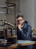 Pensive tailor sitting at a table with hand on chin in a sewing workshop. Pensive tailor sitting at table with hand on chin in a sewing workshop Stock Image