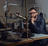 Pensive tailor sitting at a table with hand on chin in a sewing workshop. Pensive tailor sitting at table with hand on chin in a sewing workshop Stock Images