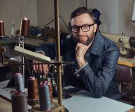 Pensive tailor sitting at a table with hand on chin in a sewing workshop. Pensive tailor sitting at table with hand on chin in a sewing workshop Royalty Free Stock Image