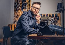 Pensive tailor sitting at a table with hand on chin in a sewing workshop. Pensive tailor sitting at table with hand on chin in a sewing workshop Royalty Free Stock Images