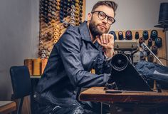 Pensive tailor sitting at a table with hand on chin in a sewing workshop. Pensive tailor sitting at table with hand on chin in a sewing workshop Stock Photo