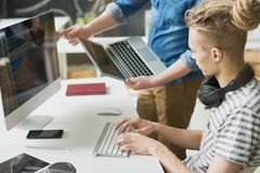 Colleagues coding information in office stock images