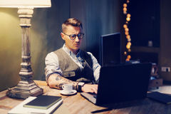 Pensive tattooed man in eyeglasses working at home on laptop while sitting at the wooden table.Using modern computer for Stock Photo