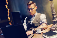 Pensive tattooed man in eyeglasses working at home on laptop while sitting at the wooden table.Using modern computer for Stock Photography