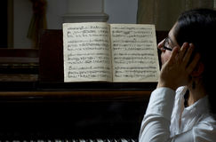 Pensive Teacher Of Music. Pensive portrait of a piano teacher sitting in profile in front of a piano, with music open on the piano stand.  Teacher seated to far Stock Images