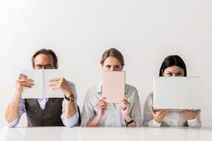 Pensive team posing with gadgets. Hiding from you. Serious colleagues are sitting at table and looking at camera thoughtfully. Mature men is covered his face Royalty Free Stock Photo