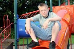 Pensive Teen Boy. Pensive teenage boy sitting on top of playground equipment royalty free stock photos